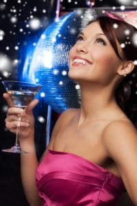Young beautiful woman at a party wearing a cocktail dress and holding a martini glass