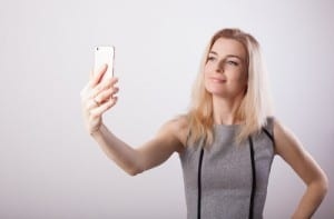 Smiling business woman making selfie photo on smartphone