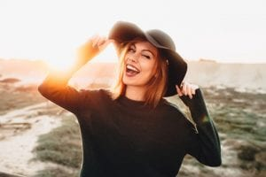 beautiful blonde young woman in glasses and holding hat and winking on the beach with sunset