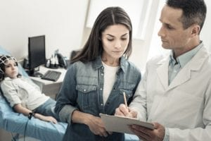 Skillful nice male doctor standing near his patients mother and taking notes