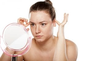img-blog-thoughtful woman looking at herself in the mirror and squeeze her ears