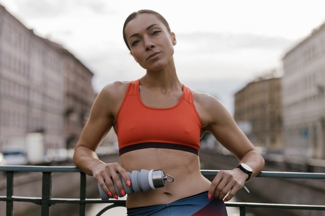 a woman in a red sports bra holding a water bottle,symbolizing activities to avoid after a tummy tuck