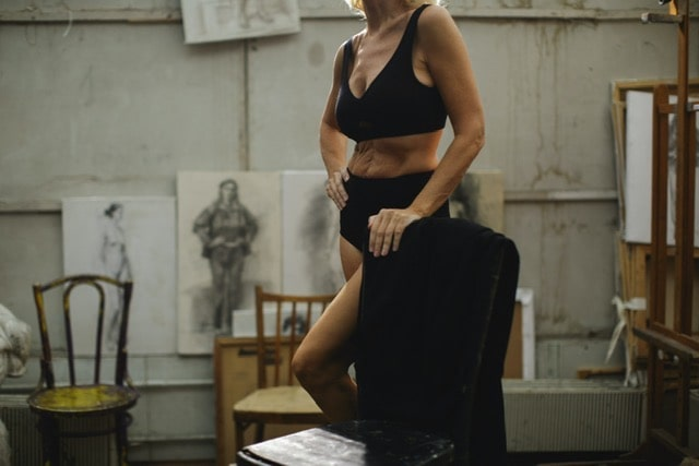 A woman posing for a painting wearing black undergarments