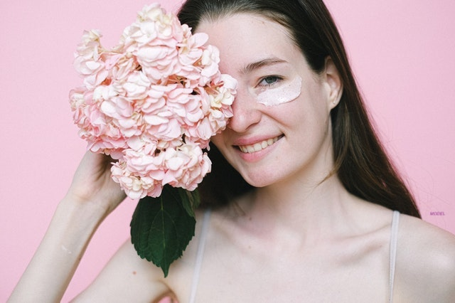 A smiling woman holding flowers with skin cream under her eyes.