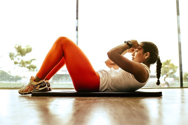 A girl exercising by doing crunches.