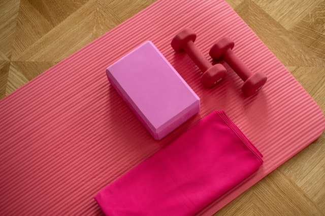 Exercising equipment, including small weights and yoga mat and blocks.
